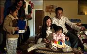 Dong Tran and his girlfriend, Hung Bui, watch as their daughter, Trish, plays with a toy she received for Christmas from an anonymous donor on Friday afternoon at the home of the Rev. Joseph Tung Dang. The family, along with Nhi Le, 4, left, who stands with her grandmother Kim Nguyen and uncle Larry Le, were among the many people displaced from their Biloxi, Miss., homes because of Hurricane Katrina. Several families moved to Lawrence after the hurricane and are trying to piece their lives back together.