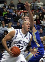 Connecticut's Ed Nelson runs under Morehead State's Clinton Reisz for a shot during the Huskies' 129-61 victory. The game was played Friday in Storrs, Conn.