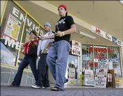Migrant workers walk by Homestead, Fla., businesses used by foreign workers to send money to their families in Central America. Immigrants send billions of dollars back to their native countries each year, especially around the holiday season, but U.S. banks have struggled to make gains in the market.