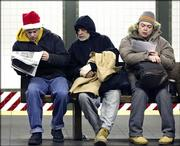 New York subway commuters read the morning paper Friday while waiting for a train. The city's buses and subways were rolling again Friday, just in time for the final rush of holiday shopping, after transit union leaders ended a costly three-day strike.