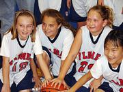 Flames Kaitlyn Jorgensen, Alexa Gaumer, Kailyn Smith, and Elena Watson pose for a picture after their win against the Lions in the Johnson County Holiday Classic Tournament in Gardner on Dec. 11.