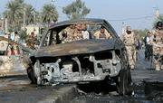 Iraqi soldiers are seen through the wreckage of a car Monday at the site of a car bomb explosion in Baghdad, Iraq. Insurgents killed at least 10 people in attacks around Iraq on Monday, including five police officers killed at a checkpoint. Attackers exploded five car bombs around Baghdad but caused relatively few casualties.