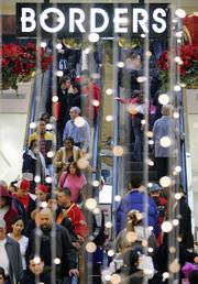 Shoppers crowd the escalators Monday at Cambridge Side Galleria mall in Cambridge, Mass.