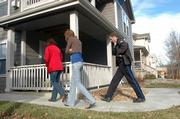 A Lawrence police officer walks with residents of an apartment in the 900 block of Mississippi. After being away from home for the holiday, the residents discovered their apartment had been burglarized.