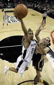 San Antonio Spurs forward Tim Duncan drives to the basket as Indiana Pacers forward Scot Pollard defends. The Spurs beat the Pacers, 99-86, Tuesday in San Antonio.