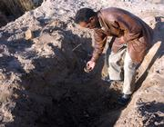 An Iraqi examines a site Tuesday where municipal workers doing maintenance work in the Shiite holy city of Karbala, Iraq, uncovered remains that police believed were part of a mass grave thought to date back to 1991, when Saddam Hussein's regime quenched a Shiite uprising in the south.