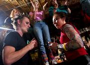 Clad in 1980s punk attire, Lawrence residents Justin and Michelle Kogl dance to retro music as other patrons of The Sandbar, 17 E. Eighth St., dance on the bar during New Year's Eve revelry Saturday night in Lawrence. The bar was the host of a retro theme for the evening, inviting tight-rolled jeans, leg warmers and loads of hair mousse.