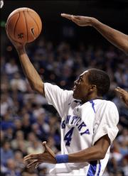 Kentucky's Rajon Rondo shoots underneath Central Florida's Justin Rose during their basketball game won 59-57 by Kentucky at Rupp Arena in Lexington, Ky. on Tuesday, Jan. 3, 2006.