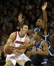 Louisville's David Padgett, left, has the ball smacked by Villanova's Kyle Lowry during first half action of their basketball game Thursday January 5, 2006 at Freedom Hall in Louisville, Ky. Behind Lowry is Villanova's Will Sheridan.