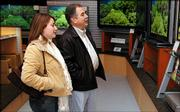 Mike Jacob and his daughter Kelly Jacob of Lawrence look at High Definition televisions at Kief's Audio Visual, 2429 Iowa Thursday. Amid the myriad of choices of HDTV's there is a minefield of settings and cables that confuse many customers.