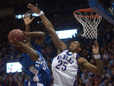 Kansas University freshman guard Brandon Rush, right, rises to block the shot of Kentucky's Joe Crawford during the first half of the Jayhawks' lopsided 73-46 rout of the Wildcats. Rush had 24 points, 12 rebounds, four assists, two blocks and a steal in the victory Saturday in Allen Fieldhouse.