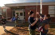 Williamstown Grade School fifth-graders Nick Alvarez, center, and Jeff Kirk remove the American flag from its pole as Caleb Richmond and Bailey Seetin work to fold the Kansas flag at the end of school Friday.