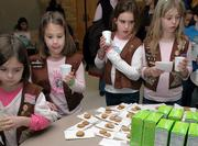 Second-graders from Troop 643, from left, Elizabeth Hansen, Domino Brewer, Eliot Eckersley and Kelty Blagg, sample the new Girl Scout cookies being offered this year during a Friday kick-off event at Southwest Junior High School, 2511 Inverness Drive.
