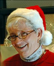 "Elaine Skoch, Eudora, serves food at the community Christmas dinner at First United Methodist Church in Lawrence. It was Skoch&squot;s first time to volunteer at the annual meal. ""I&squot;ve had a ball,"" she said."