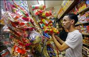 Roque Feliz rearranges packages of potato chips Wednesday in a Harlem deli in New York. The city's health department is launching a drive to improve the offerings on the shelves of local bodegas as part of Mayor Bloomberg's new initiative to get New Yorkers to eat better.