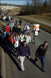 Tteachers and students walk up Crestline Drive on Kansas University's west campus toward the Lied Center.