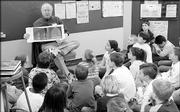 "Greg Garrison, from CMP Publishers in Lawrence, reads ""The Polar Express"" to third-graders at Broken Arrow School for a LEAP partnership. He visited the school in December 2005."
