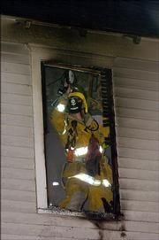 A Lawrence and Douglas County firefighter looks for hot spots in the walls of a building at 1322 Massachusetts.