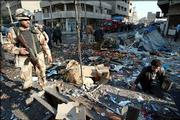An Iraqi soldier walks through wreckage and debris after a roadside attack in Baghdad, Iraq. Early reports say that two near simultaneous suicide and roadside bomb blasts Thursday killed at least 12 people. The explosions are part of a surge of violence this week in Iraq.
