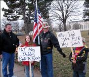 Kevin Nikes, left, president of Local 919 of the American Federation of Government Employees, talks with Brandin Raney, center, and his children, Samantha Raney, 10, and Logan Raney, 8. The Raneys, from Weston, Mo., joined prison workers at the U.S. Penitentiary to protest staff reductions and other issues.