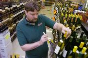 Scott Schmidtberger, a manager for Alvin's Wine and Spirits at 4000 W. 6th St., goes through his wine supply as he dusts off the bottles on Friday. A Kansas Senate bill would allow customers to purchase wine over the Internet or telephone.