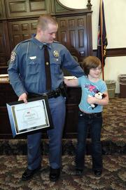 Douglas County Sheriff's officer Adam Hoover, left, gets a hug from his daughter Samantha, 8, after Hoover was awarded the Medal of Valor for his actions during the Boardwalk Apartments fire in October. Awards were handed out to nine deputies Tuesday at the Douglas County Courthouse.