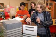 A team of eighth-graders from West Junior High School will be participating in Future City regional competition Saturday at Kansas University. From left, students Dravid Joseph, Dylan Guthrie and Sam Walter work on a model of the industrial side of their future city, which is a 2050 concept of a geothermal-driven city in Iceland.