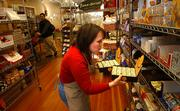 Lora Wiley, owner of Au Marche, 931 Mass.,stocks the shelves of her European grocery and gift shop. Wiley opened the store more than seven years ago.