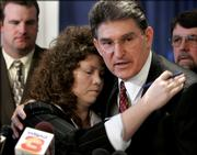 West Virginia Gov. Joe Manchin hugs Delorice Bragg, wife of mine fire victim Don Bragg, after signing mine safety legislation Thursday at the Capitol in Charleston, W.Va. State lawmakers passed the legislation unanimously.