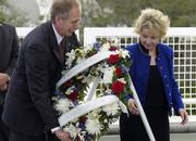 William Gerstenmaier, associate administrator for Space Operations at NASA, and June Scobee Rodgers, widow of Dick Scobee, Challenger's commander, place a wreath at the base of the Space Mirror Memorial on Saturday during a ceremony for the Challenger astronauts at the Kennedy Space Center.