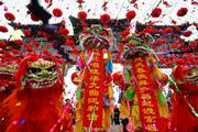 "Chinese performers dressed in traditional lion costumes display two banners reading ""Sing songs showing harmony to end the year of the rooster, with the approaching of the year of the dog, singing and dancing across Beijing."" They danced Saturday during the opening ceremony of the Earth Park Temple Fair as the nation celebrated the Lunar New Year during Spring Festival in Beijing."