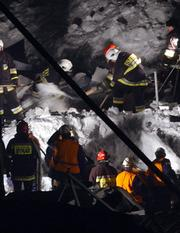Rescue workers remove snow and rubble of a collapsed roof of the International Fair building in Katowice, southern Poland. The roof collapsed during a pigeon show Saturday, killing at least 33 people and trapping hundreds.