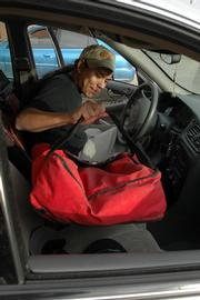 Chris Moore, a student at Haskell Indian Nations University, gets ready to make a delivery for Pizza Shuttle. Jeff Morris, manager of Pizza Shuttle, is concerned about violent attacks on his company's delivery drivers.