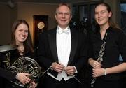 Annie Kettle, left, and Merry Chadwick are pictured with Timothy Mahr, director of the St. Olaf Band. The 2003 Free State High School graduates will play a musical homecoming with the band at 7 p.m. today at the high school, 4700 Overland Drive.