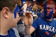 KU student Branden Seuell, a Kearney MO, freshman paints the face of Paul Wallace, a Garden City freshman during pregame of the Texas Tech game Monday at Allen Fieldhouse.