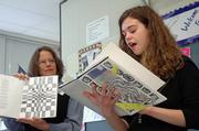"Pamina Buechner, right, an eighth-grader at West Junior High School, reads from ""Broken,"" a book of poems she wrote and illustrated, while teacher Lynn Burlingham displays the illustrations. West students read from their books Tuesday during an Author&squot;s Tea at the school. The students&squot; books will be placed in the school library."
