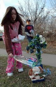 Children lay flowers at a memorial site near the intersection where Bryce Olsen, 6, was killed in an accident Monday. Bryce's death has touched many in his neighborhood, and brought a renewed emphasis on safety.