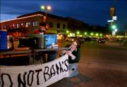 Lawrence residents Kim Coughlin and Wesley Teal, members of the group Food Not Banks, hang a banner and prepare a table of free food Wednesday evening at the corner of Ninth and Massachusetts streets outside the US Bank building. The group provides a free meal to anyone in need.