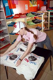 Erin Adams, manager at Joe College store, organizes a table of KU basketball announcer, Max Falkenstien T-shirts at the new T-shirt shop at 734 Mass.