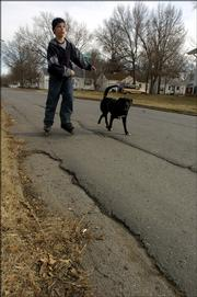 Braxton Vardys, 13. Lawrence, along with his dog Bella, avoid the bad part of 21st and Tennessee as he was out  skating Monday afternoon.