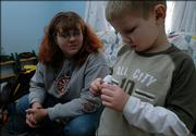 Amanda Griffith watches her son Lucas,5, play with one of his hermit crabs Monday afternoon. Griffith is a single mom who hasn't seen any child support payments from her ex-husband since last summer. She's finding is very difficult to raise Lucas and a newborn on her salary alone.
