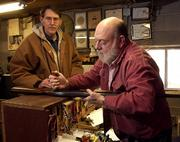 Lawrence gunsmith Doug Coffman puts the finishing touches on a shotgun he repaired for Lawrence resident Doug Yoder, left, Wednesday afternoon at Coffman's Repair and Custom Gunsmith Shop. As an avid gun enthusiast, Coffman sees nothing wrong with the idea of carrying a concealed weapon as long as the individual passes a background check and receives proper training on handling firearms.