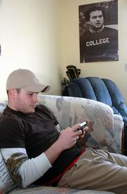 KU junior Mike Moeller plays a video game on a portable PlayStation in his Lawrence apartment. Moeller, who had a bad experience with a past landlord. Other KU student tenants are urging the Legislature to enact safeguards against unfair landlords who assess exorbitant cleaning fees and other charges.