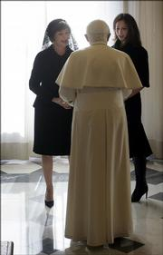 U.S. first lady Laura Bush, left, and her daughter, Barbara, speak with Pope Benedict XVI on Thursday in his private library in Vatican City.