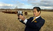 Osamu Yoshida takes photographs Friday afternoon at the Tailgate Ranch south of Tonganoxie. Yoshida was among a Japanese delegation visiting the U.S. to discuss concerns about mad cow disease. Fears of the disease have led to a ban of U.S. beef imports to Japan.