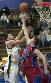 Haskell Indian Nations University senior Brandon Stevens shoots over a Newman University defender. The Fightin' Indians won, 62-61, Saturday at Coffin Sports Complex.