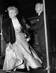 A smiling President Harry S. Truman helps his wife, first lady Elizabeth Truman, from their car in front of a Washington hotel in this April 2, 1952, file photo, as they arrive for a dinner at which they entertained Queen Juliana and Prince Bernhard, of the Netherlands.