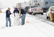 From left, Brandon Sunbury, Jacob Hill and Andrew Gibson build a snowman Saturday in the median off Interstate 65 near Franklin, Ind. The trio was stranded with hundreds of other motorists for more than two hours after a multi-vehicle accident closed the interstate.