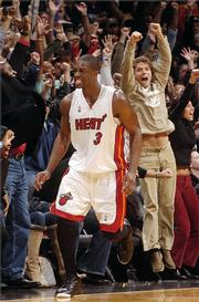 Miami's Dwyane Wade celebrates with the hometown crowd after hitting the winning shot in the final seconds against Detroit. Wade's bucket helped give the Heat a 100-98 victory over the Pistons on Sunday.