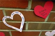 Hearts on the wall of Sunset Hill school contain suggestions for the family members of one of the school's students whose family's home was damaged in a fire Tuesday. People can pick up one of the suggestions and drop off the items at the school where they will be given to the family.